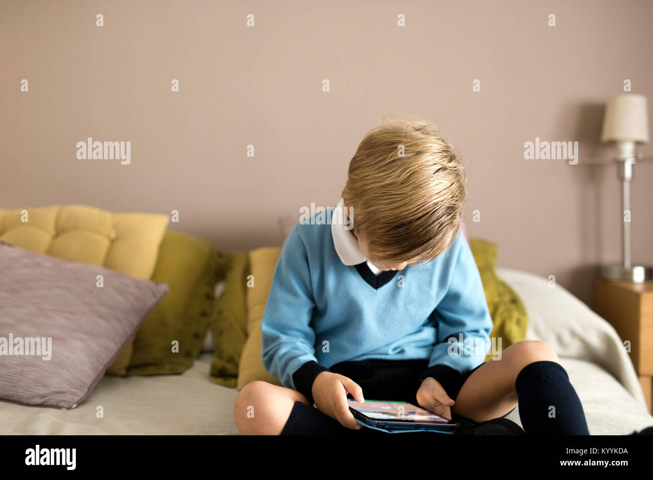 Boy using digital tablet dans la chambre à coucher dans la chambre à coucher Banque D'Images