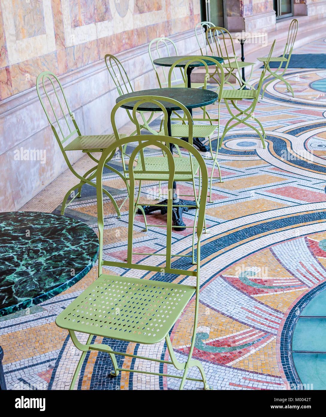 Chaises et tables de jardin vert sur un carrelage en mosaïque à la ...