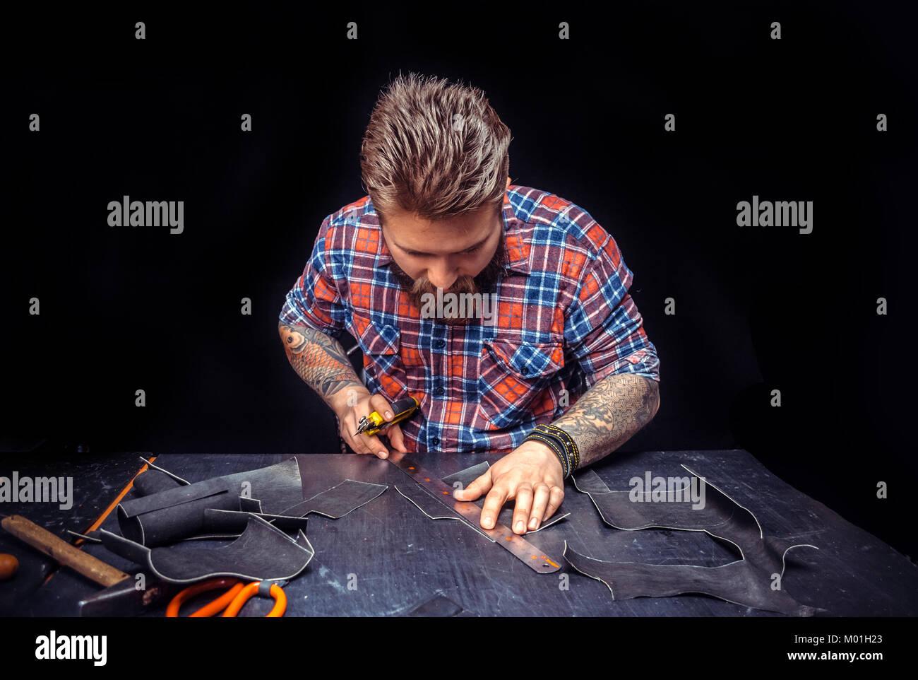 L'accent professionnel en cuir sur son travail à son workshelf./Currier travaille sur un nouveau produit en cuir Banque D'Images