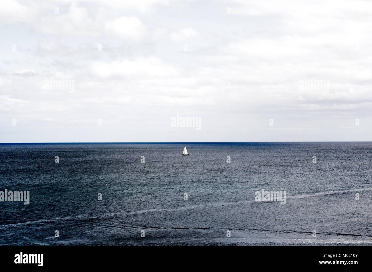 La voile sur mer sous ciel nuageux au large de la côte de Mevagissey, Cornwall Banque D'Images