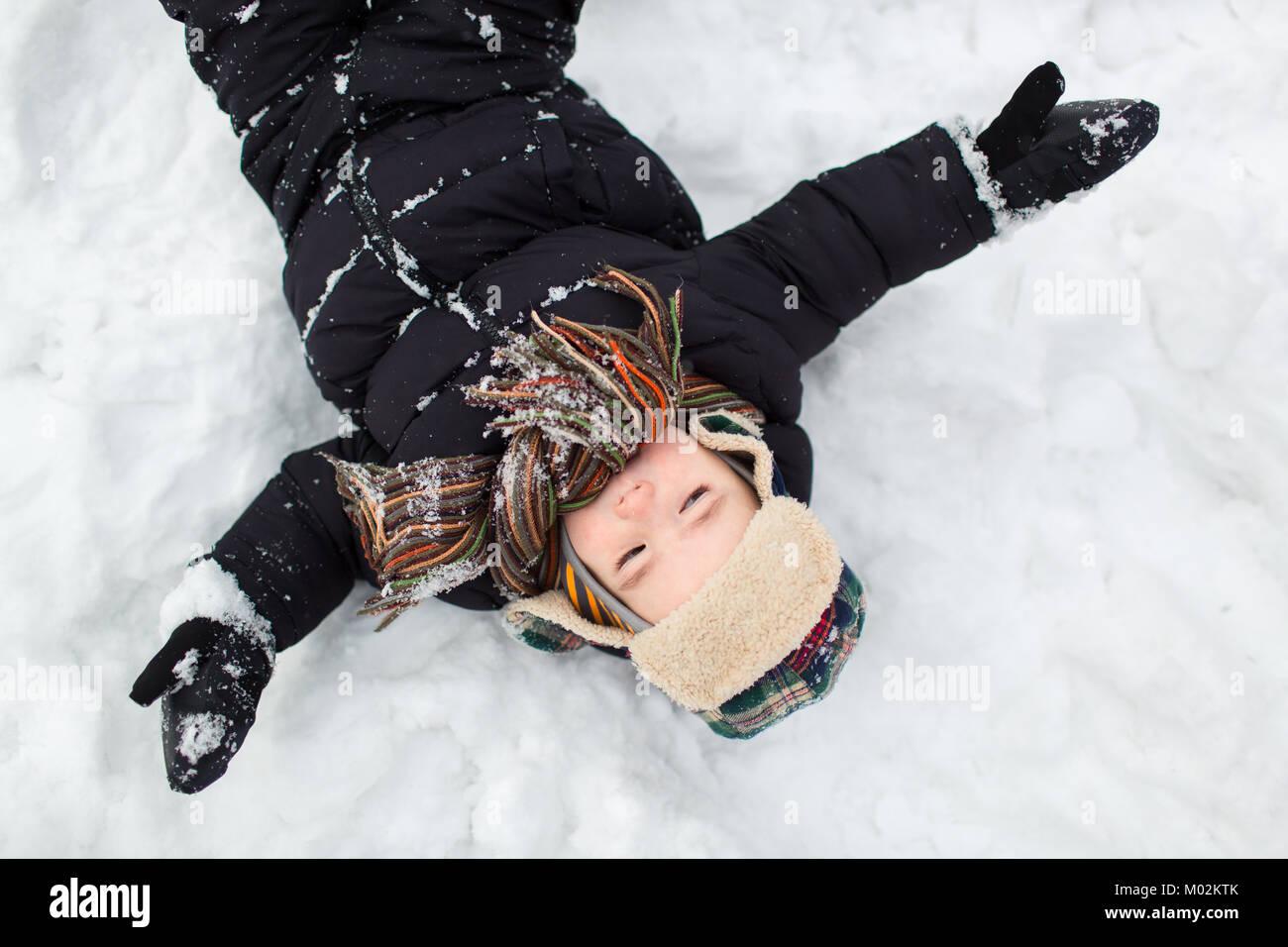 Vue de dessus d'un petit enfant vêtu de vêtements chauds avec les bras étendus de large dans Photo Stock