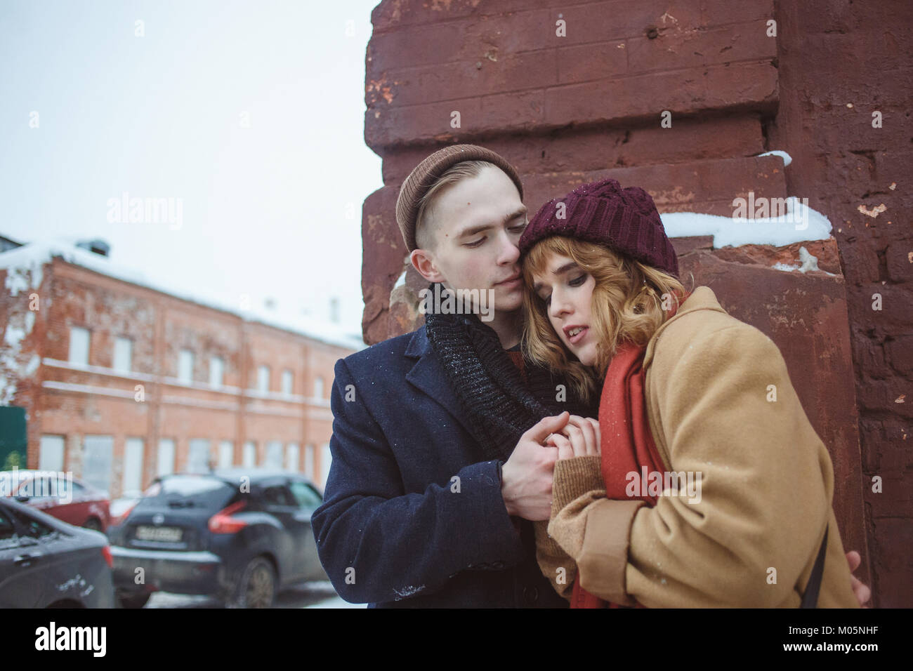 Young man and woman embracing près de brick coin de bâtiment. Rue d'hiver. La vie privée dans Photo Stock