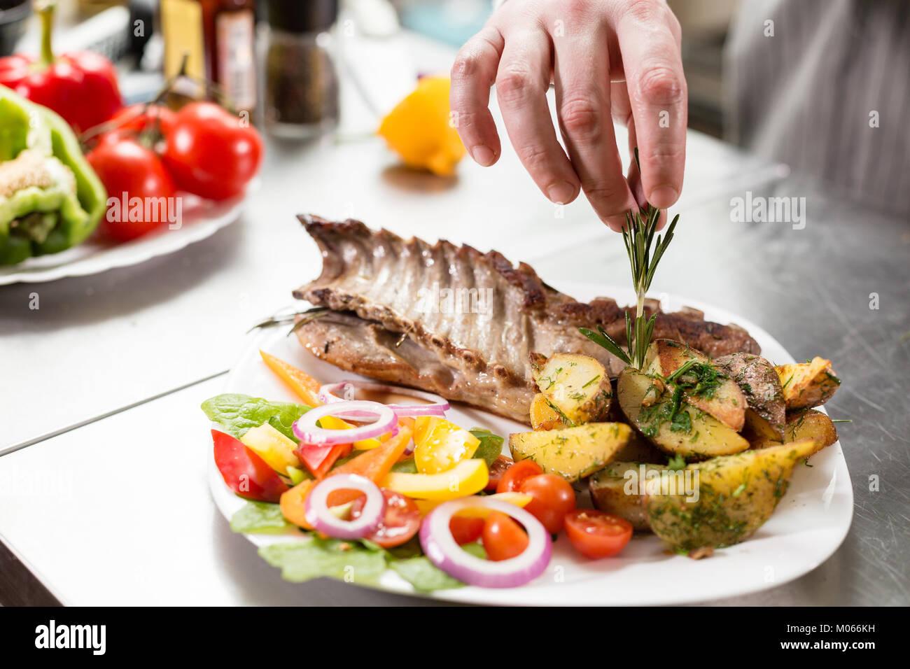 Décoré avec une branche de romarin. Le chef vous prépare au restaurant. Carré d'agneau grillé Photo Stock
