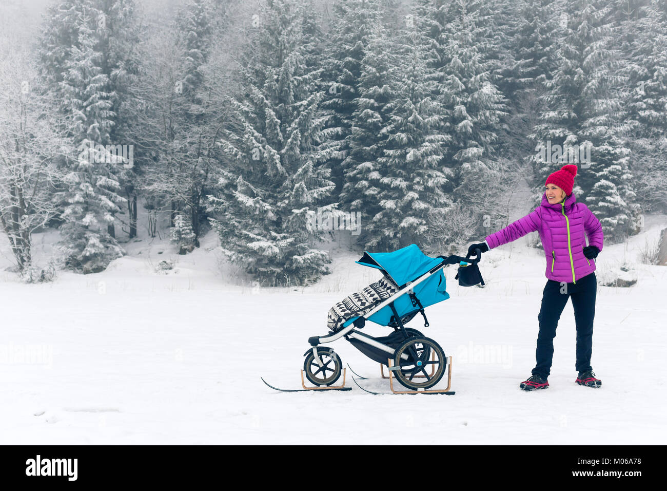 Maman avec poussette de bébé profiter de la maternité dans la forêt d'hiver, paysage montagneux. Photo Stock