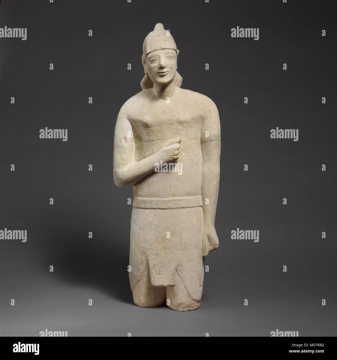 Statuette en pierre calcaire d'un homme imberbe votary dans Egyptianizing dress portant un casque rencontré DP204726 Banque D'Images