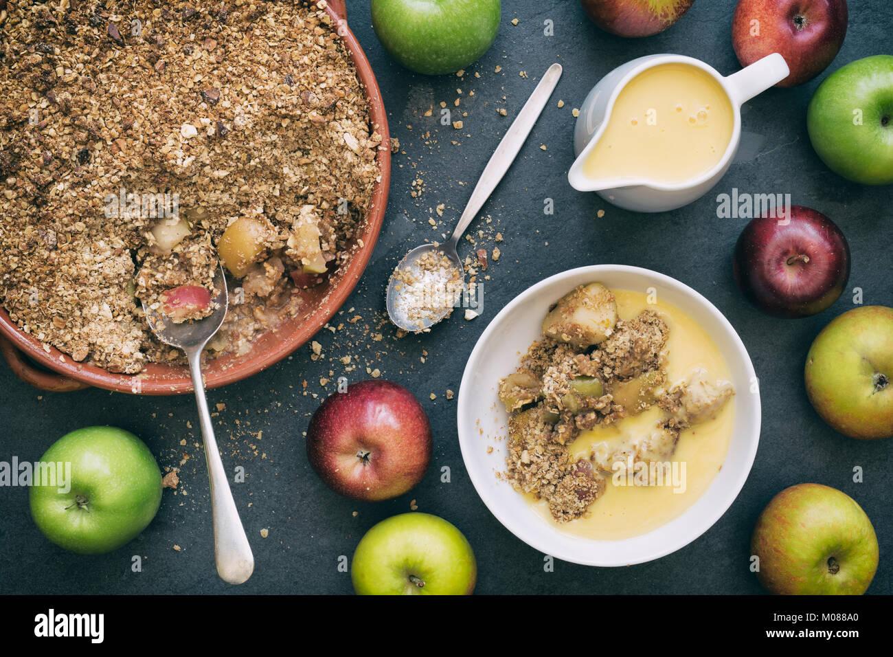 Crumble aux pommes, crème anglaise et pommes fraîches sur un fond d'ardoise Photo Stock