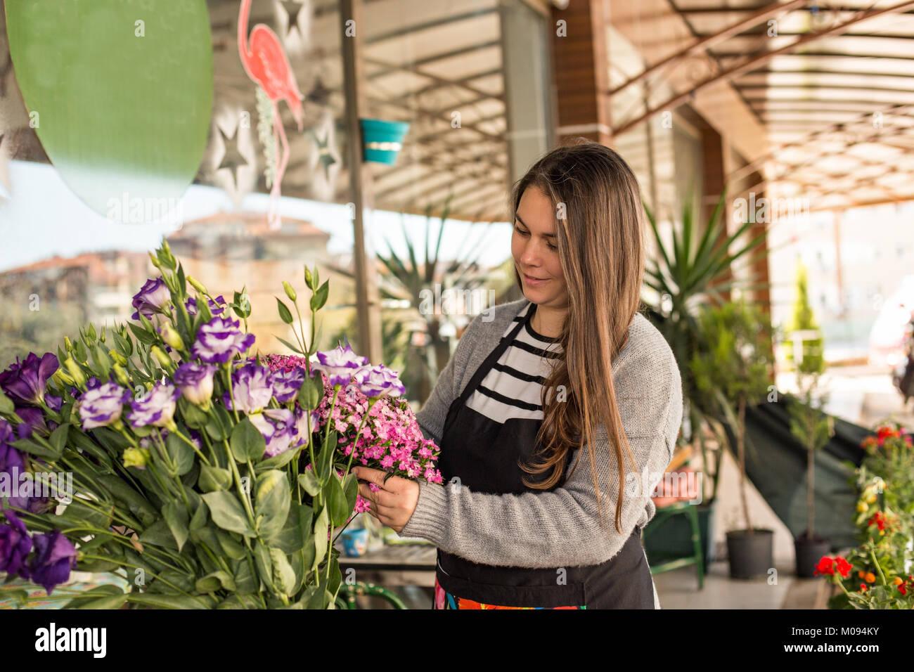 Small business concept. Femme Smilng la cueillette des fleurs fleuriste dans un magasin de fleur. Composition horizontale Photo Stock
