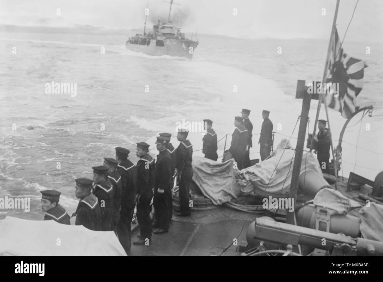 L'équipage de la marine sur un autre navire japonais salue et vole le drapeau de l'Amirauté Photo Stock