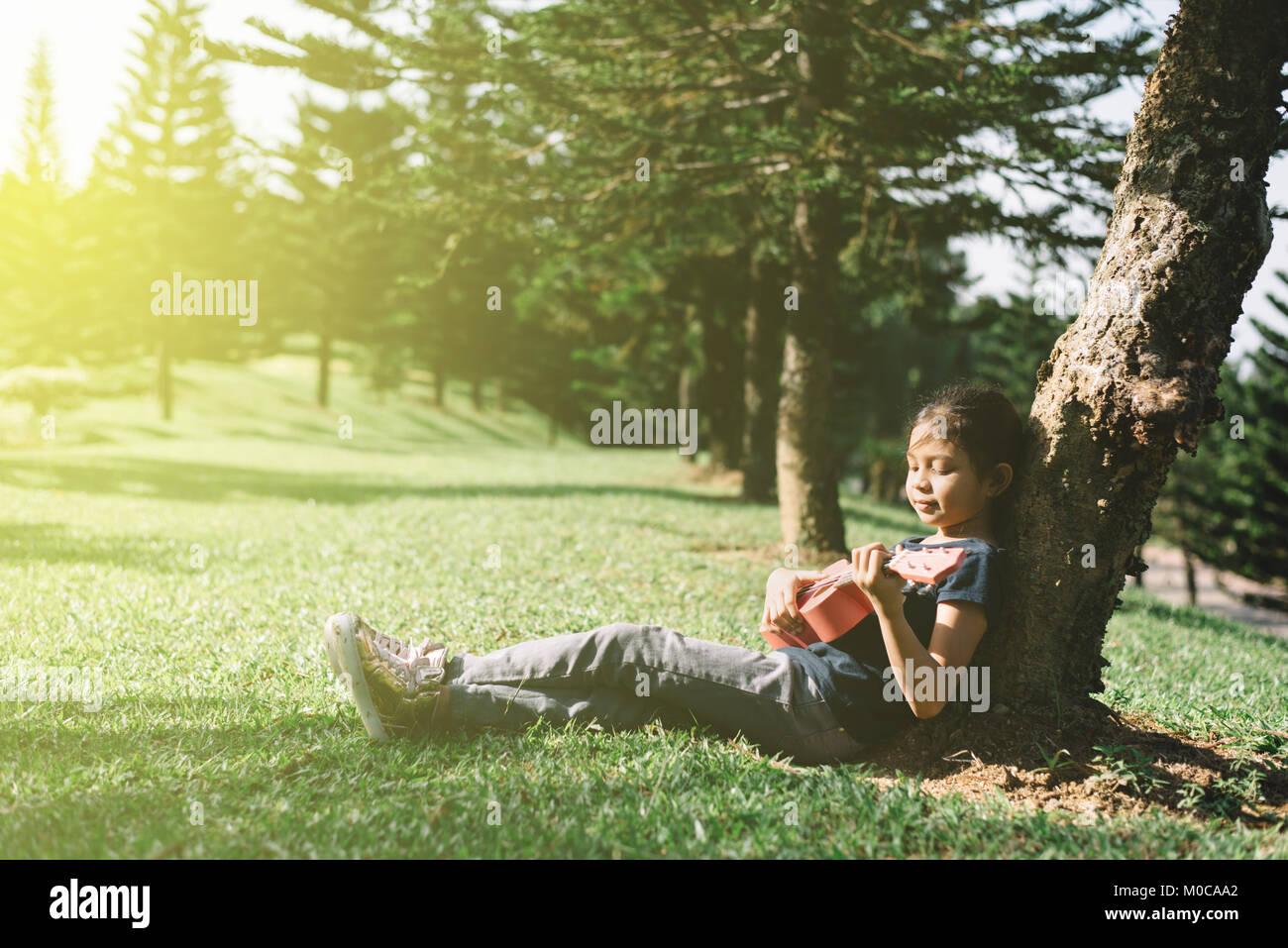 Les jeunes et happy asian girl Playing with ukulélé guitare au parc sous le soleil de matin. hobbies et Photo Stock