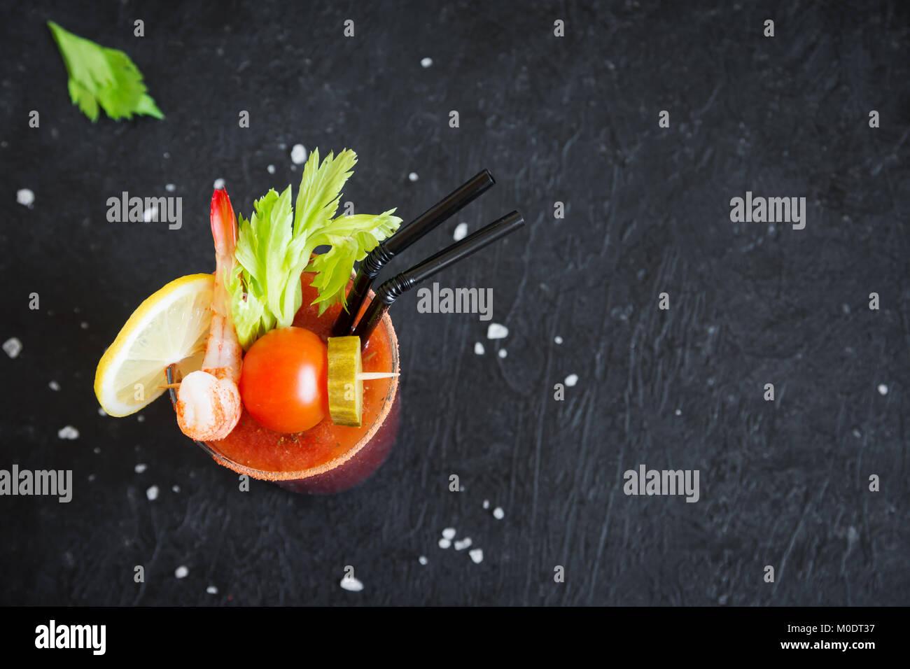 Cocktail Bloody Mary en verre avec des garnitures. Bloody Mary tomate boisson épicée sur fond noir avec Photo Stock