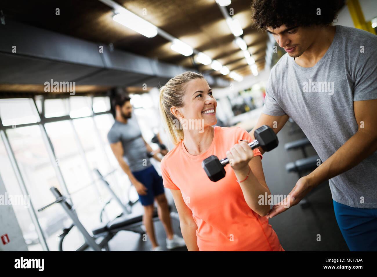 Belle jeune femme faisant des exercices avec un entraîneur personnel Photo Stock