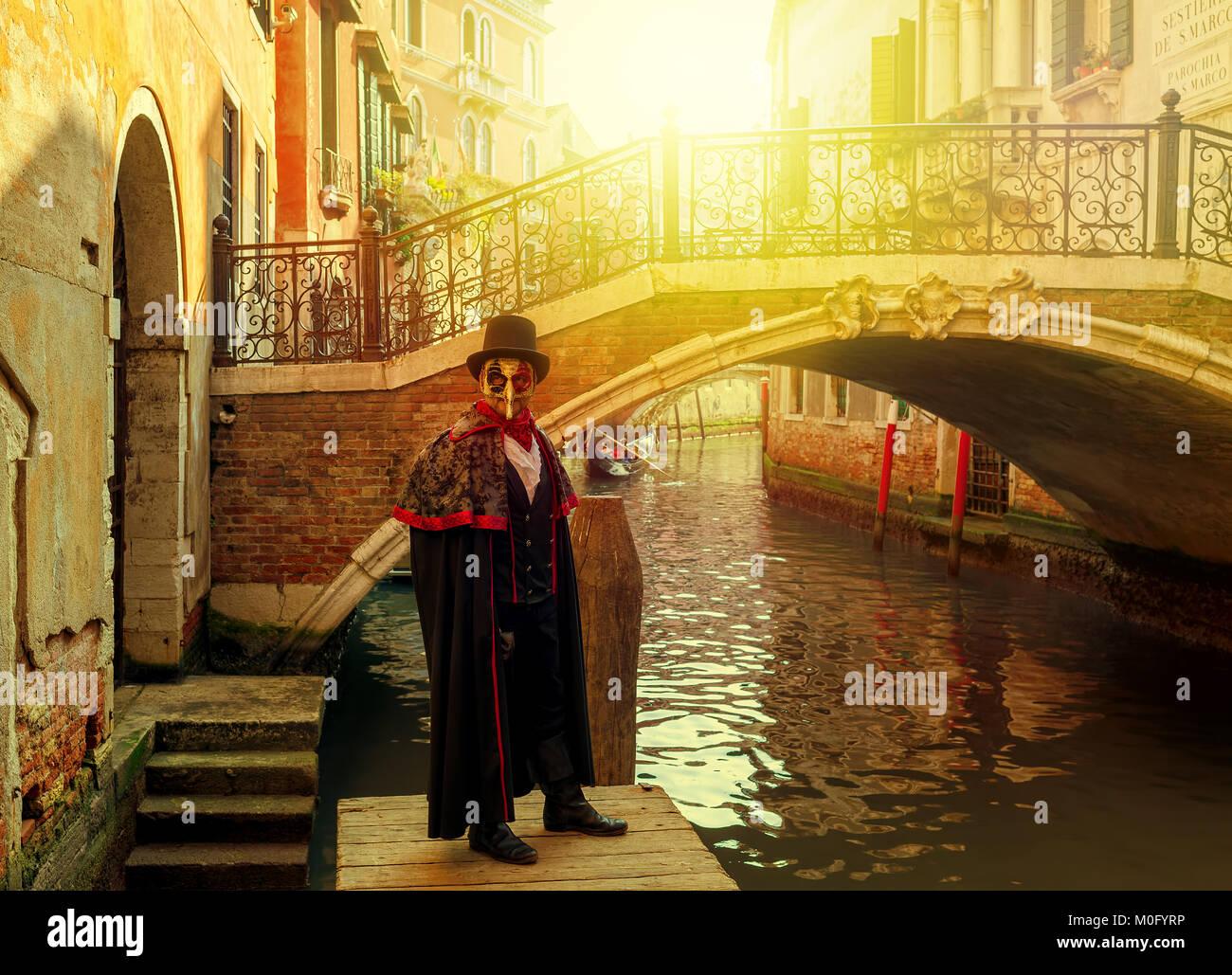 Homme non identifié en costume noir, chapeau et masque devant un petit pont au-dessus de l'étroit canal vénitien Banque D'Images