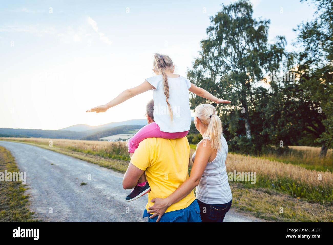 L'exécution de la famille sur le dos de l'enfant à pied l'été Photo Stock