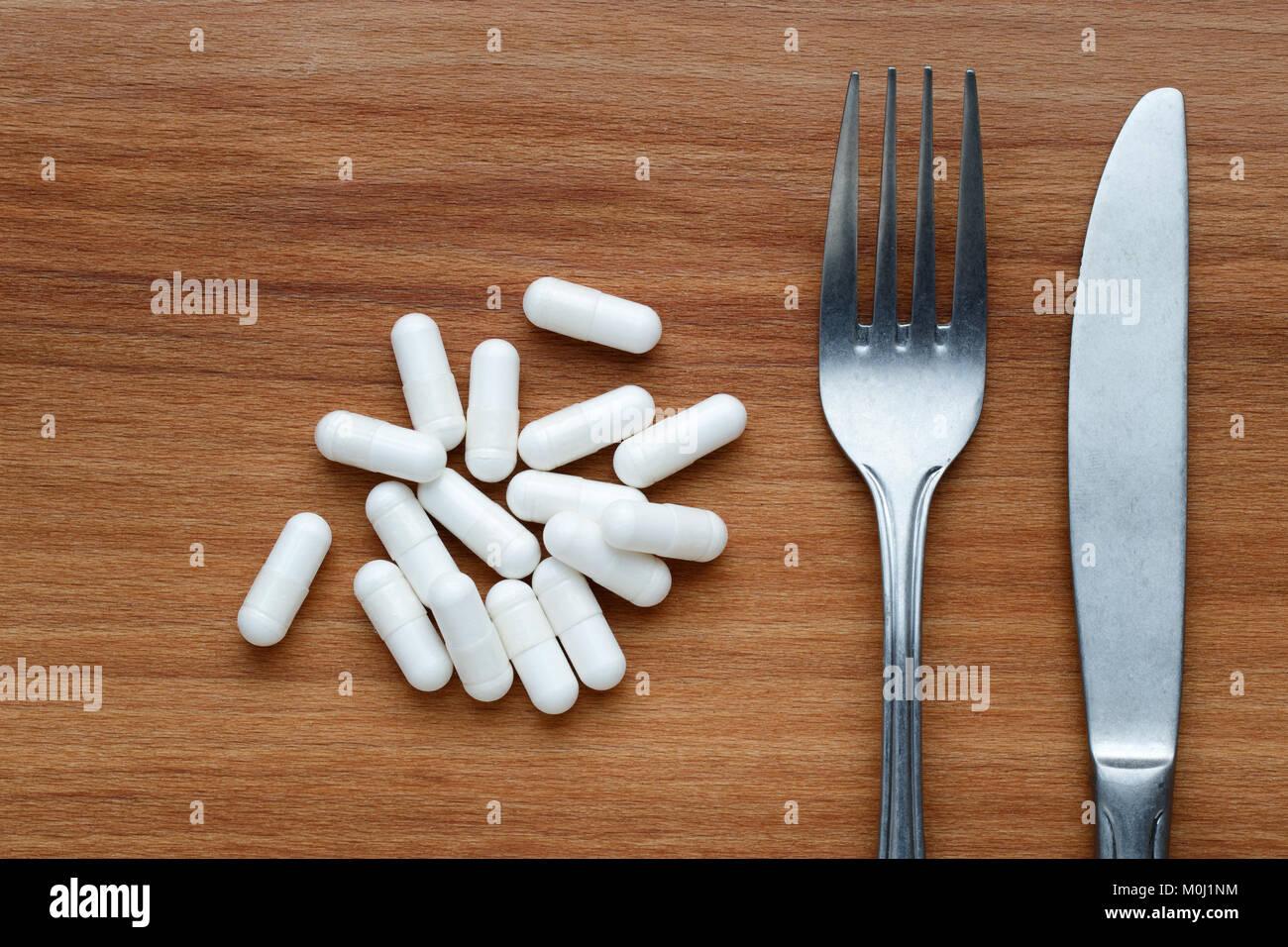 Concept de régime avec supplément pills, couteau et fourchette Photo Stock