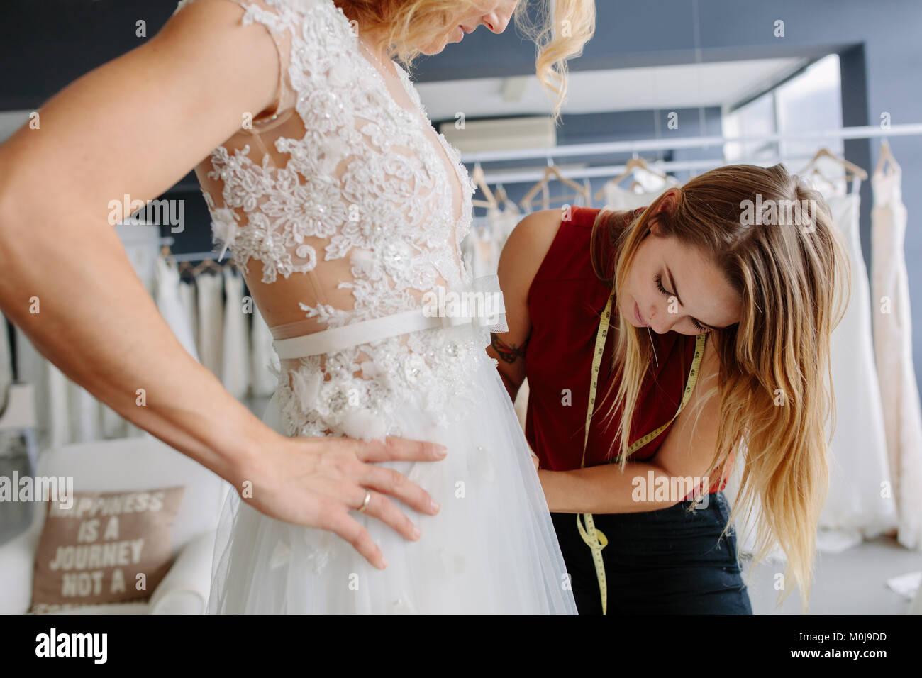 Robe habile montage designer robe de mariage pour femme dans la boutique. Femme d'effectuer des réglages Photo Stock