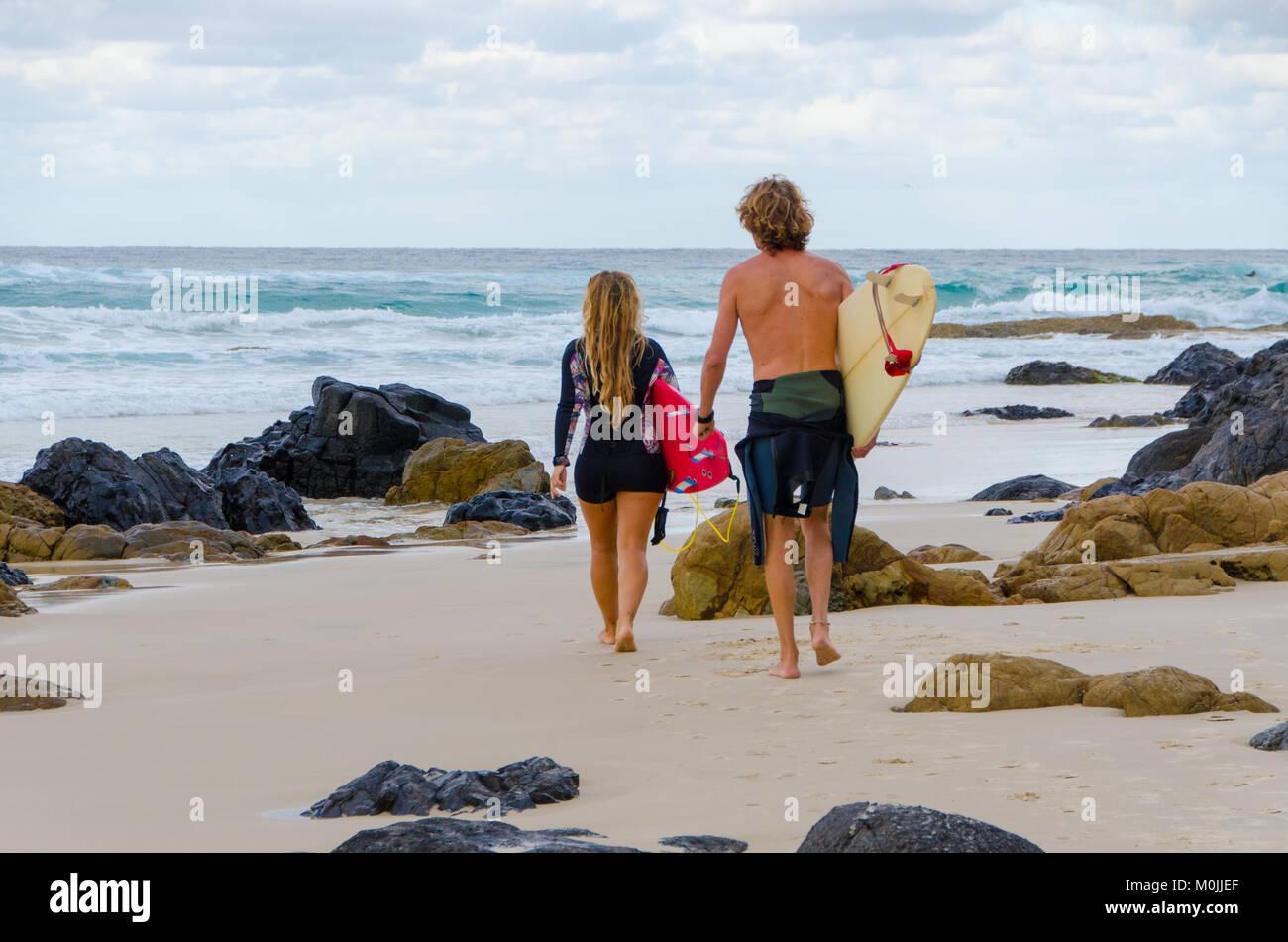 Surfers mâles et femelles à pied à travers l'océan plage vers l'exécution des planches Photo Stock