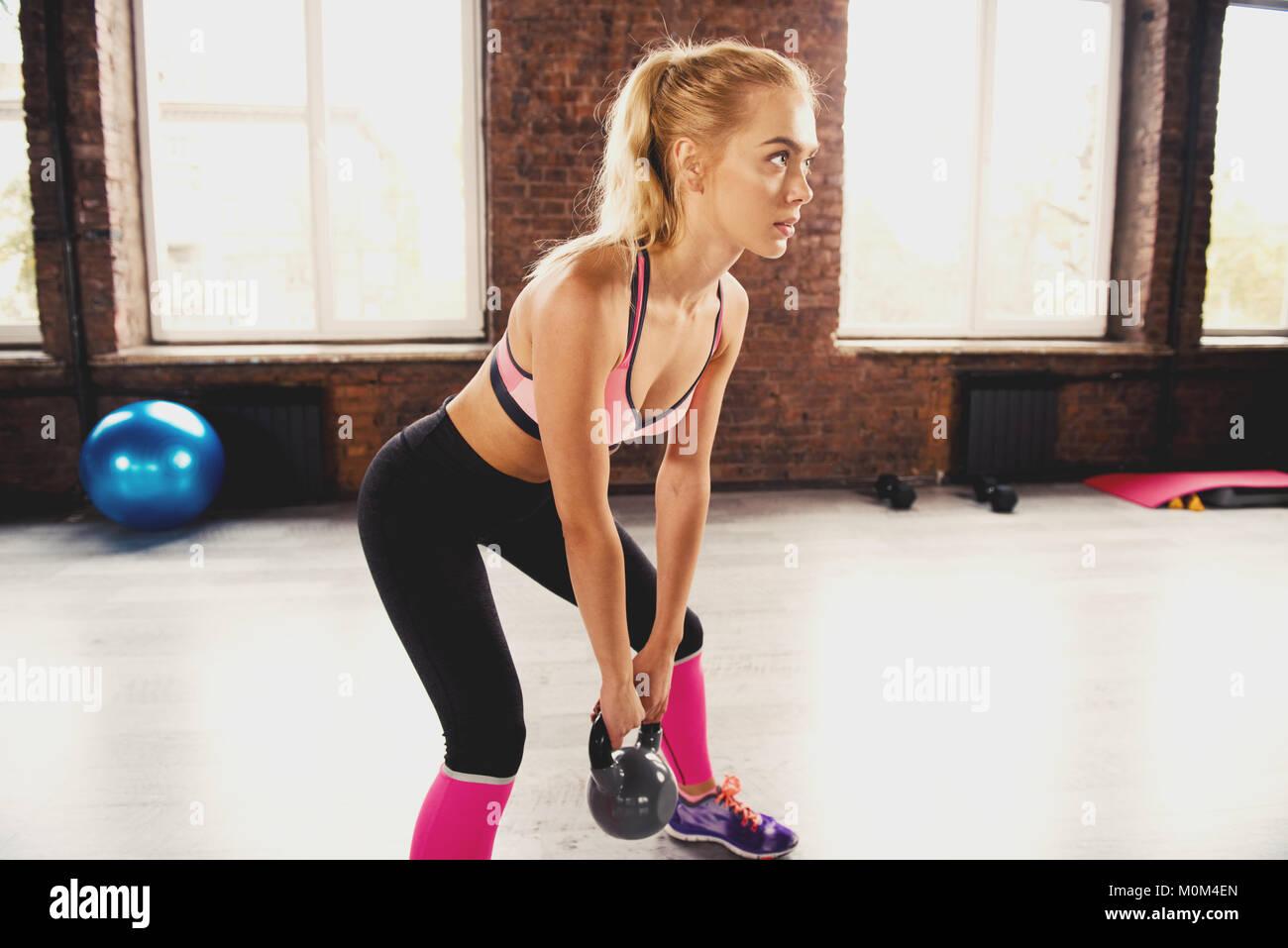 Jeune fille blonde à la salle de sport avec un kettlebell exercice crossfit. Photo Stock