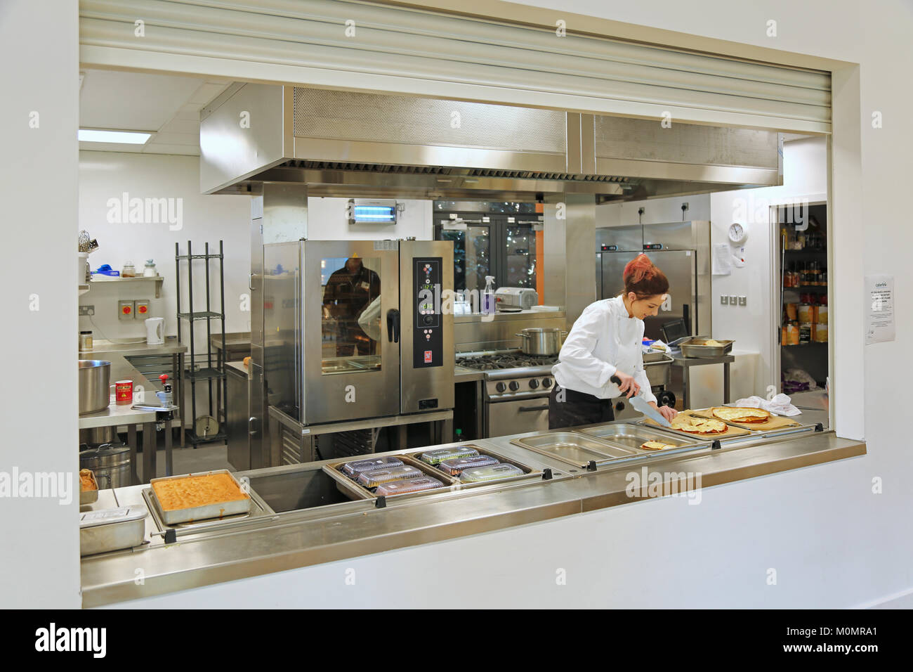 Un assistant de restauration prépare les repas scolaires dans une école primaire de New London, UK. Banque D'Images