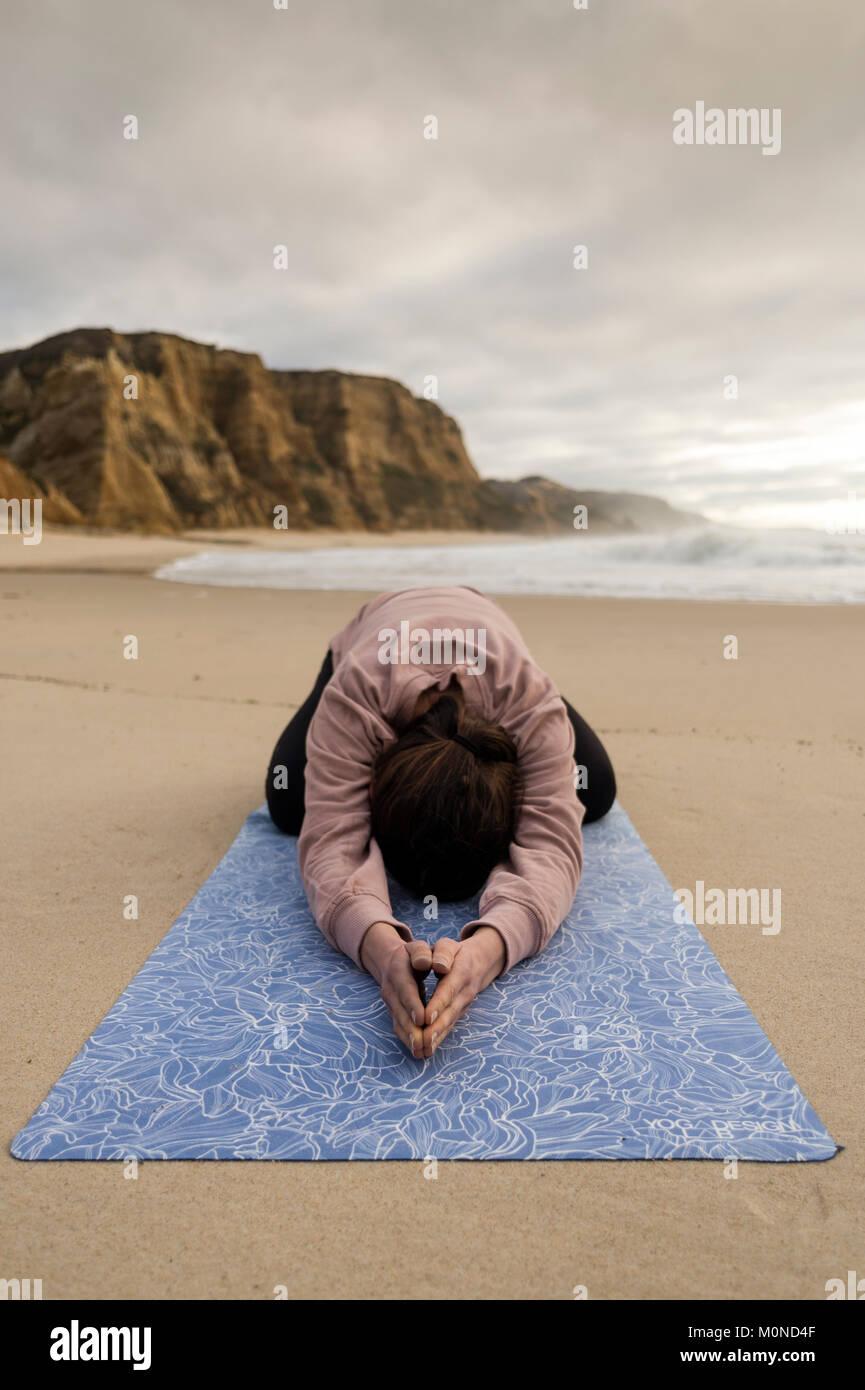 Woman practicing yoga faisant une posture de l'enfant à la plage Photo Stock