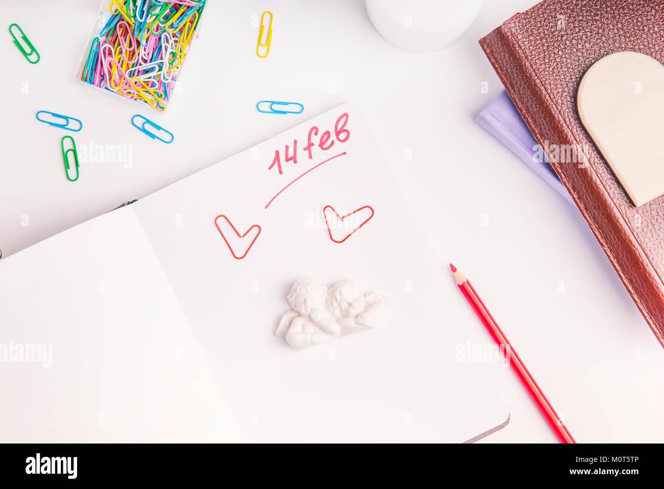 Numéro de l'écriture rouge 14 février, jour de la Saint-Valentin et les anges texte stauette organiseur personnel sur sur le lieu de travail. Concept de planification de la Saint-Valentin. Focus sélectif. Banque D'Images