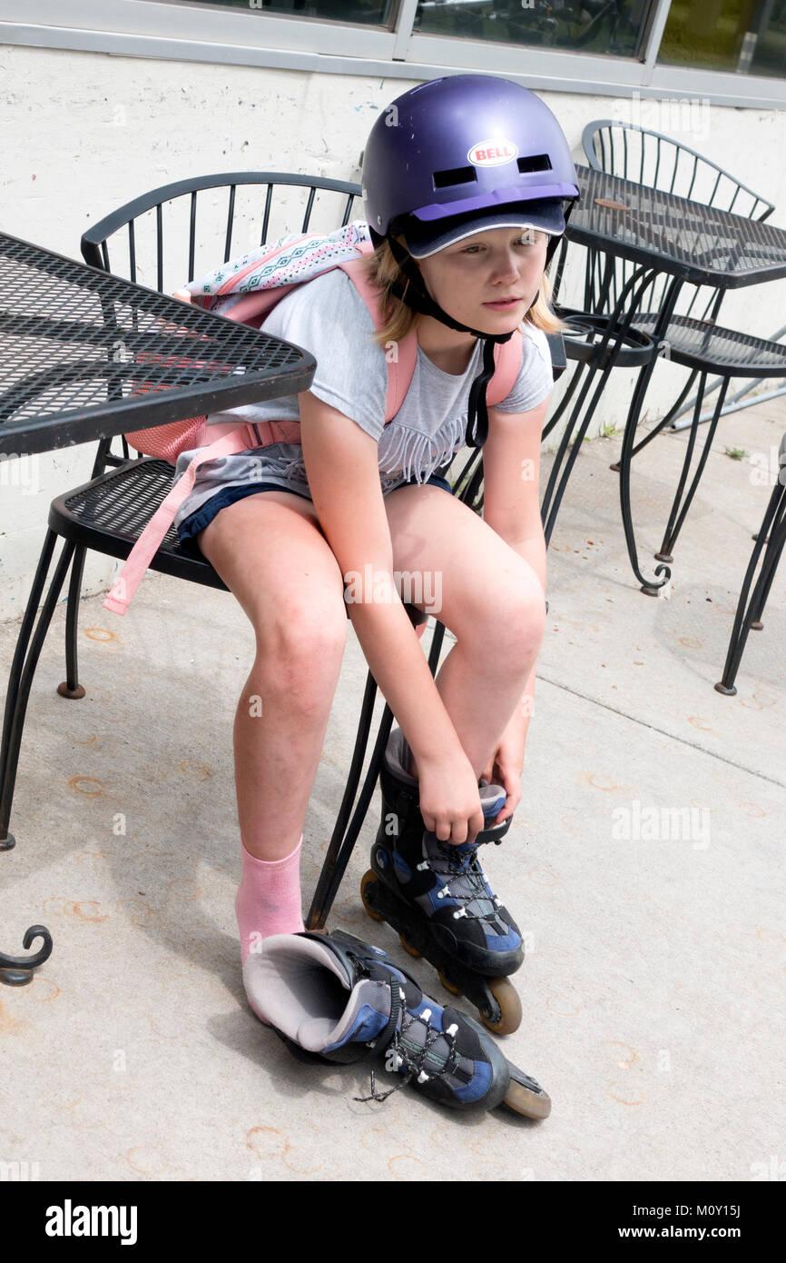 L'âge de 10 ans fille fatigué dépose ses rollers en ligne le port d'un casque de sécurité. Photo Stock