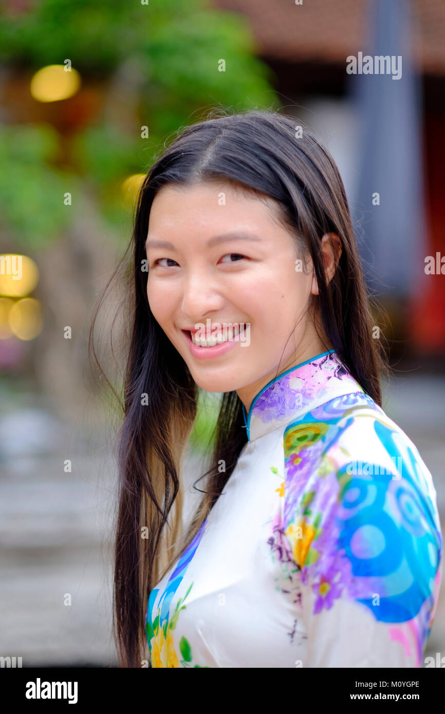 Vietnamese woman smiling et portant une robe traditionnelle Ao Dai Photo Stock