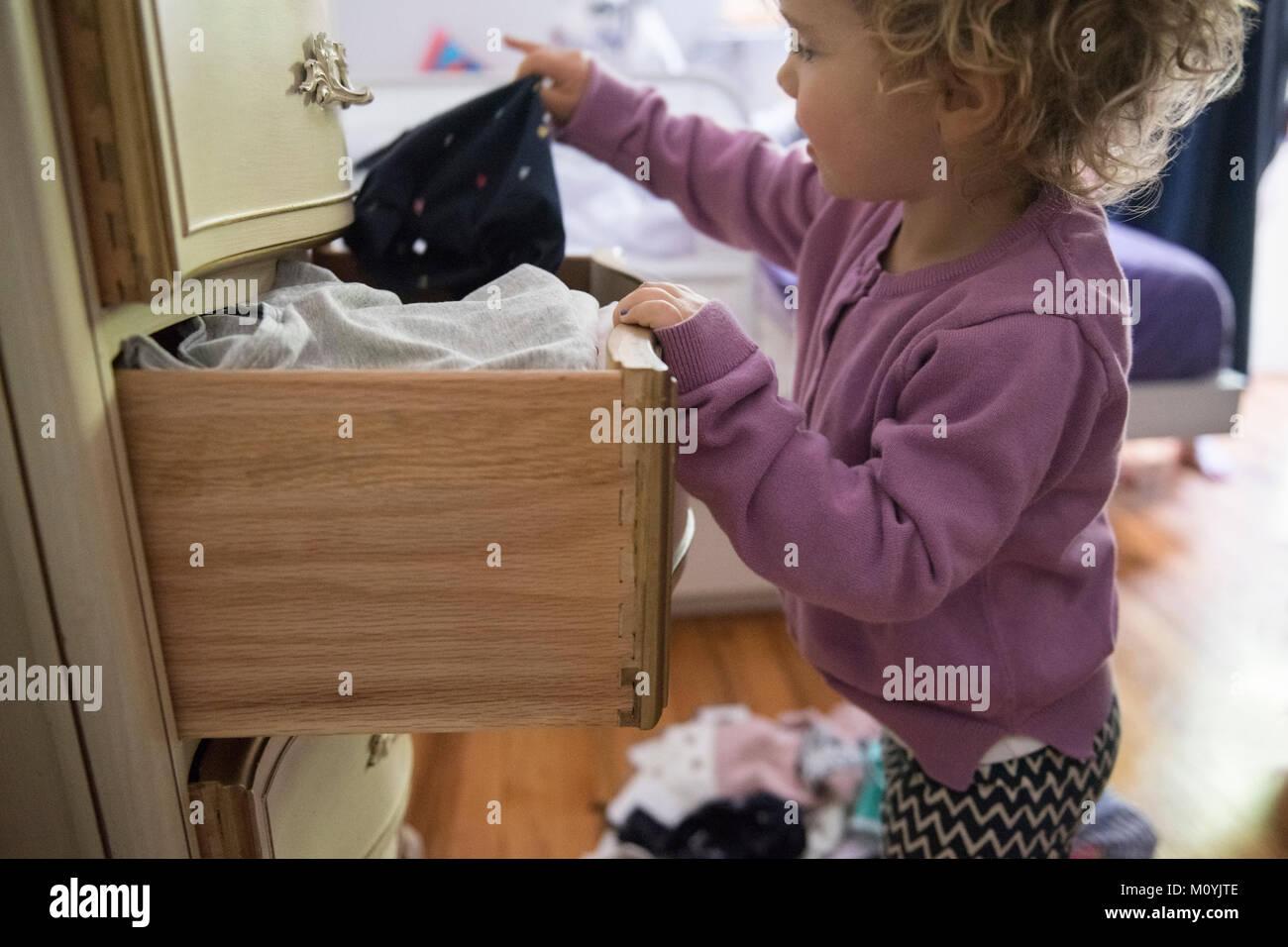 Caucasian girl dépose de vêtements à partir de tiroir Banque D'Images
