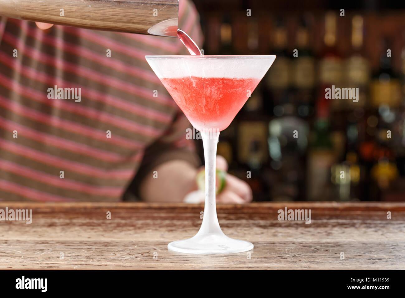 Cocktail Cosmopolitan, le barman se déverse sur le bar. Cocktail sur la base de vodka, de triple-sec, liqueur de citron et jus de canneberge. Un espace réservé au texte Banque D'Images