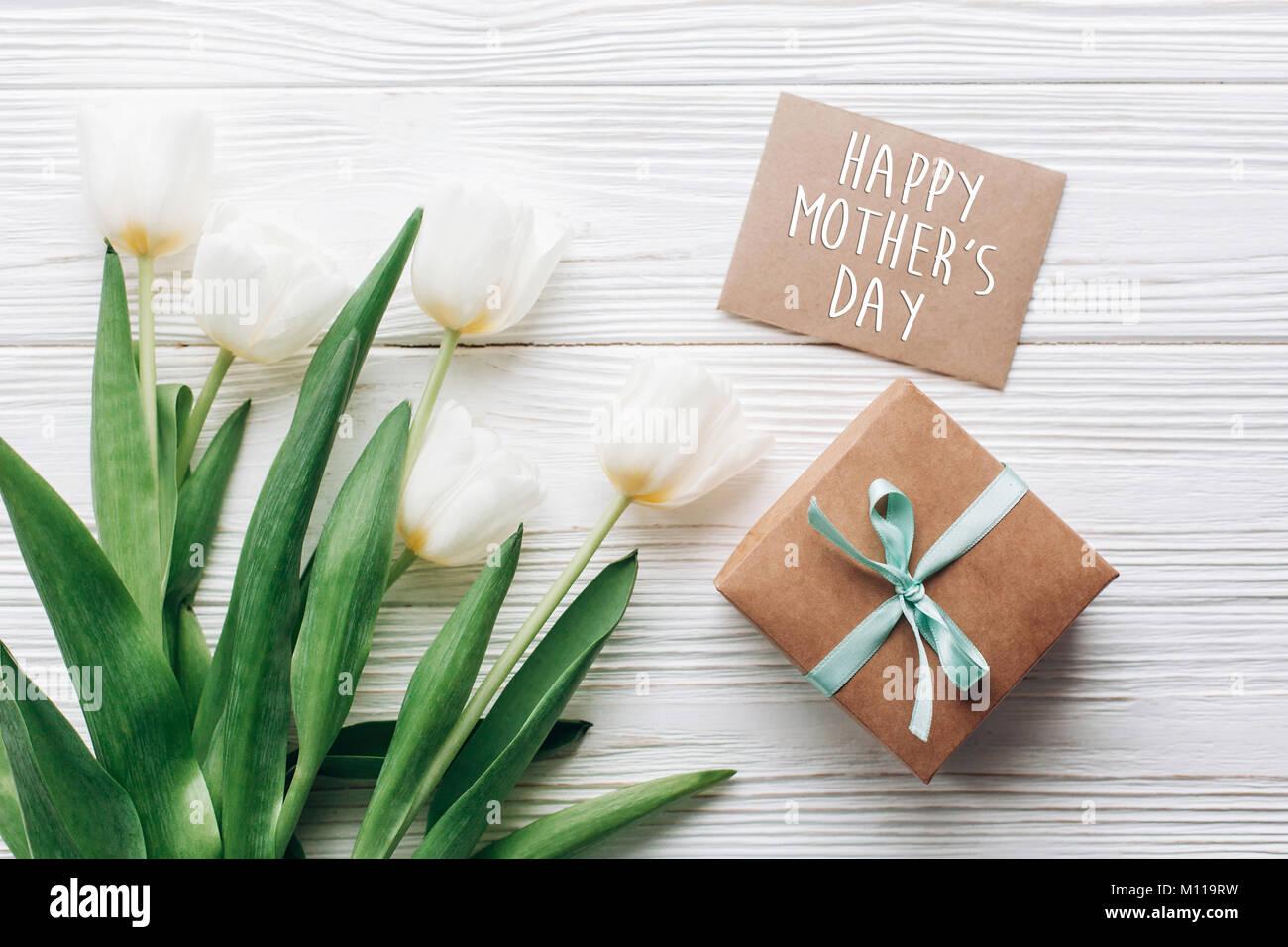 35a992e3d9de Happy mothers day text signe sur l artisanat présent fort élégant et carte  de souhaits et des tulipes sur fond rustique en bois blanc.