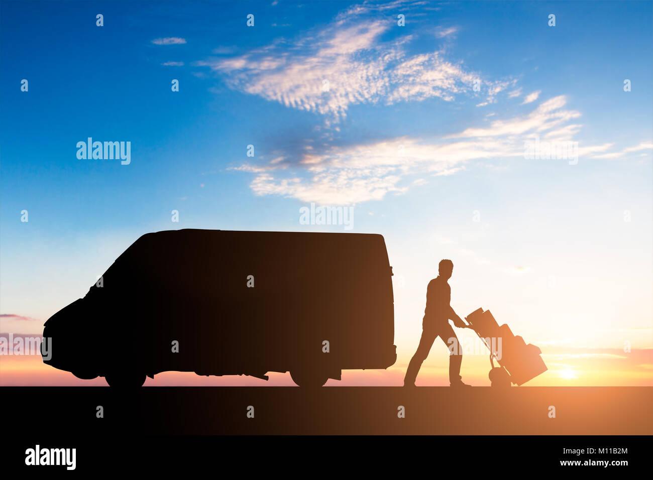 Silhouette de messagerie livraison avec des boîtes en carton sur chariot près du Van au coucher du soleil Photo Stock
