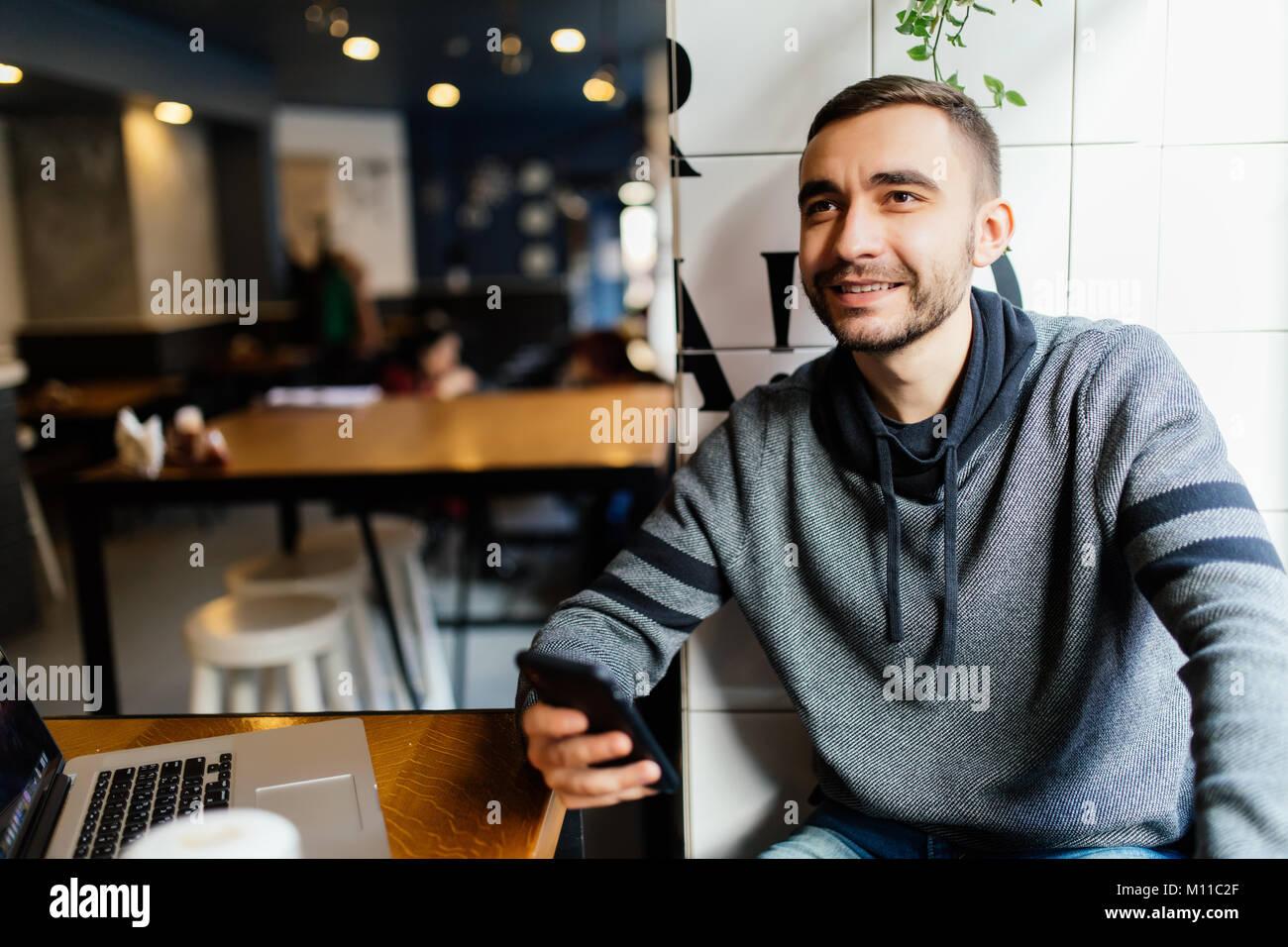 Close-up of male hands holding et à l'utilisation de smart phone in cafe shop. L'envoi de l'homme moderne les nouveaux Banque D'Images
