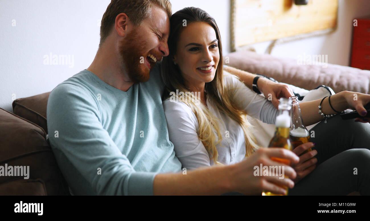 Couple heureux de boire une bière et toasting at home Photo Stock
