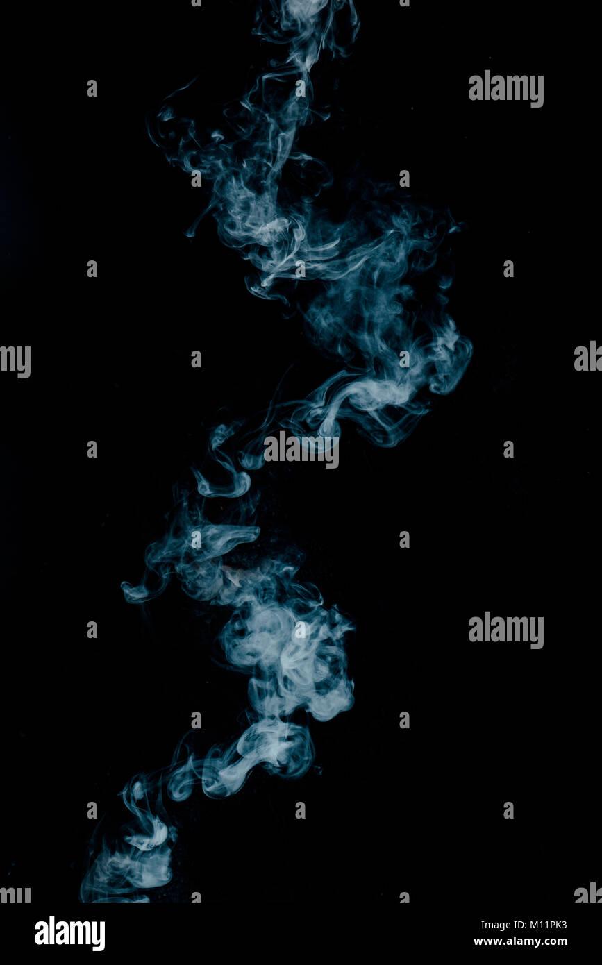 La texture de la vapeur d'une boisson chaude sur un fond noir. Fumée bleue avec copie espace. Photo Stock