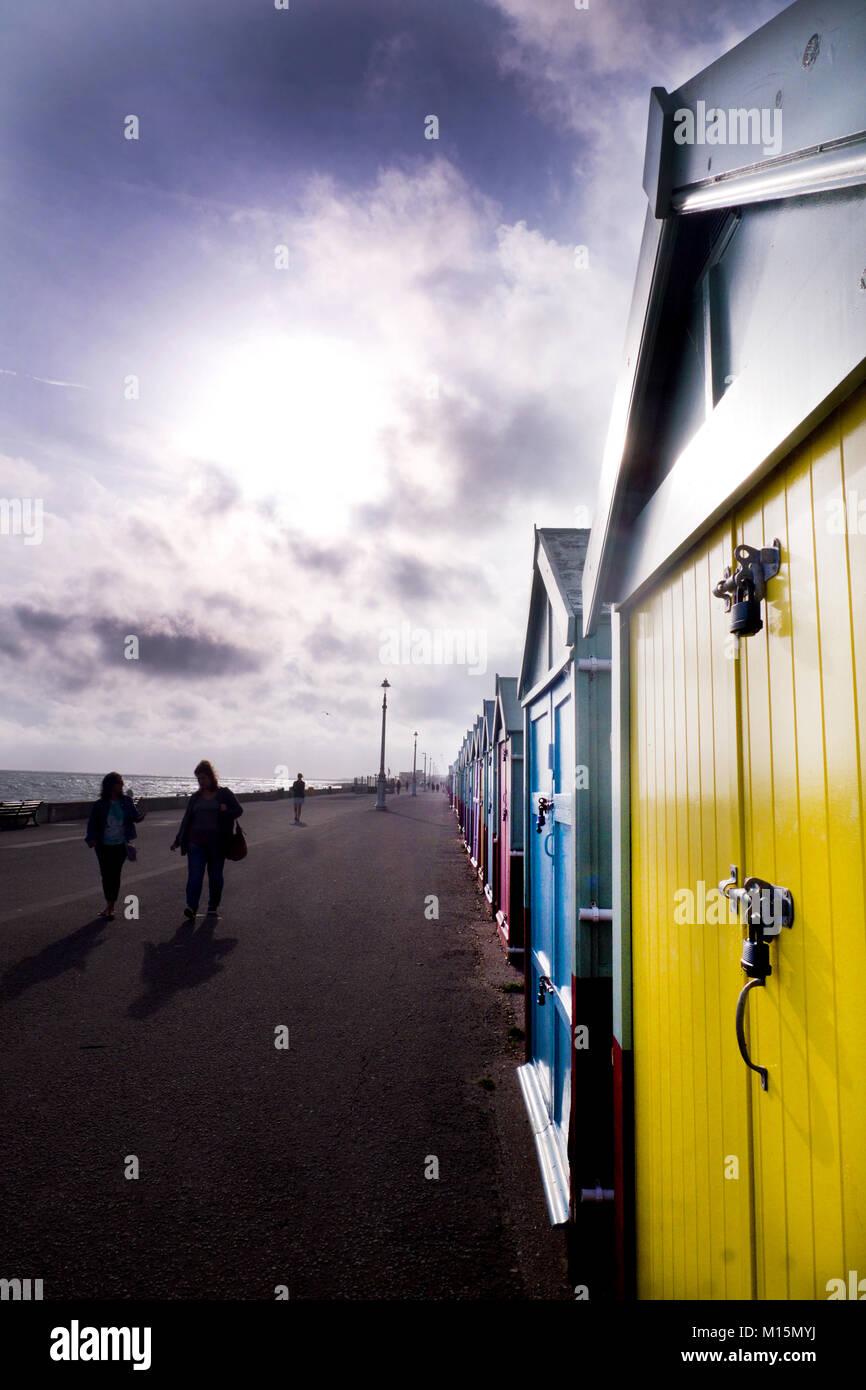 La plage de Brighton, promenade sur la droite une rangée de cabines colorées allant de grande ou petite Photo Stock
