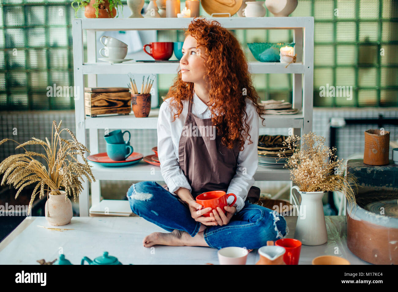 Redhead woman sitting in lotus pose dans l'argile shop Photo Stock