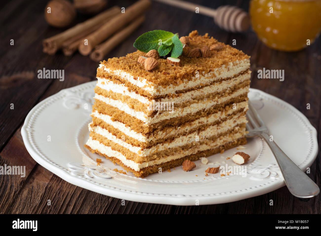 Tranche de gâteau de miel en couches le russe Medovik décoré avec des amandes et menthe on white Photo Stock