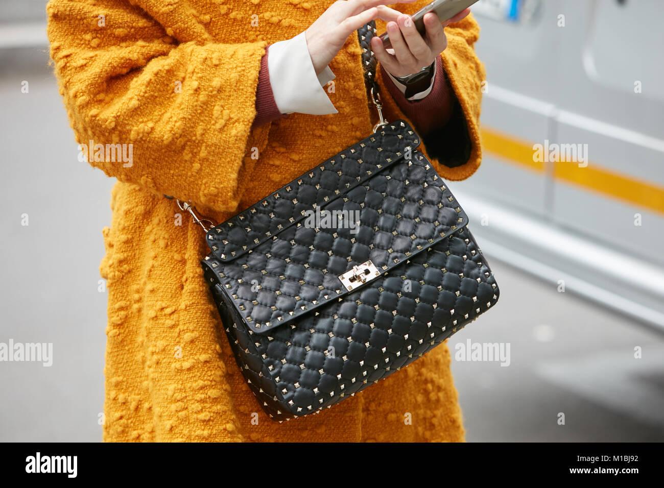 0815cc73c0cf MILAN - janvier 15   Femme avec sac en cuir noir avec clous en or jaune