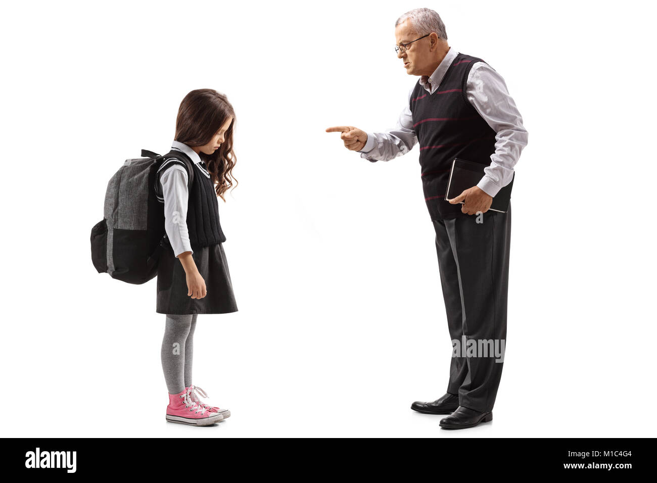De toute la longueur d'une ancienne enseignante de réprimandes une écolière isolé sur fond Photo Stock