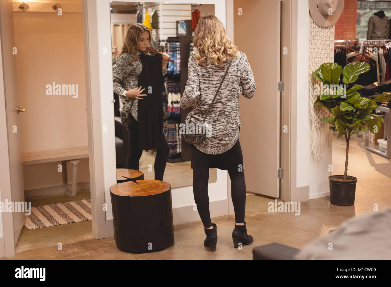 Rear view of woman checking out dress Photo Stock