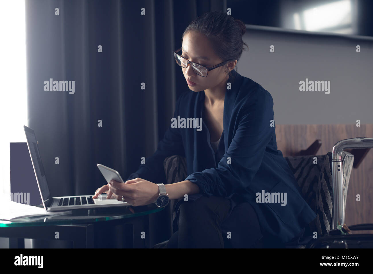 Woman using mobile phone and laptop at table Banque D'Images