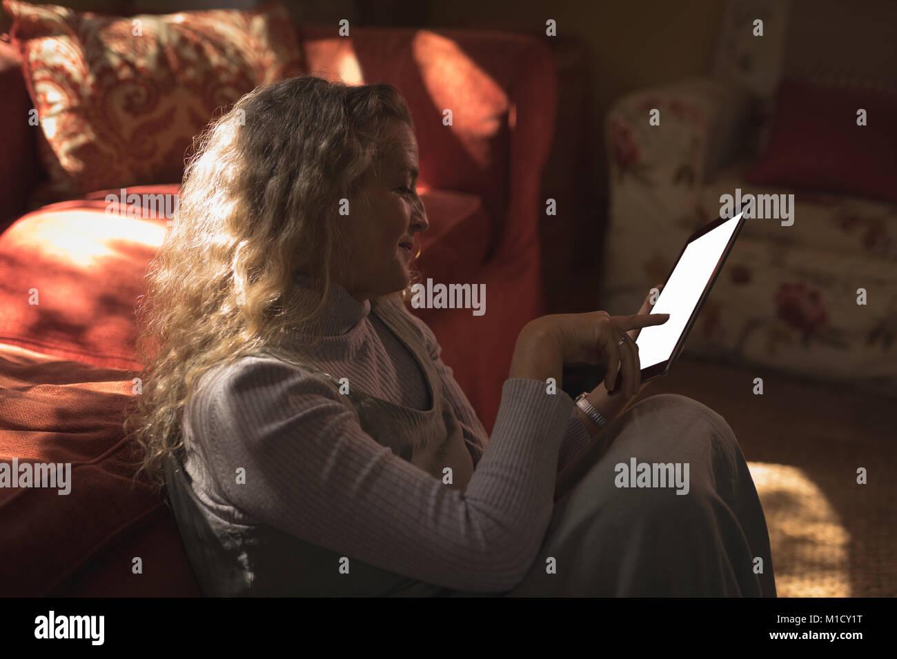 Young woman sur le sol et en utilisant son tablet Photo Stock