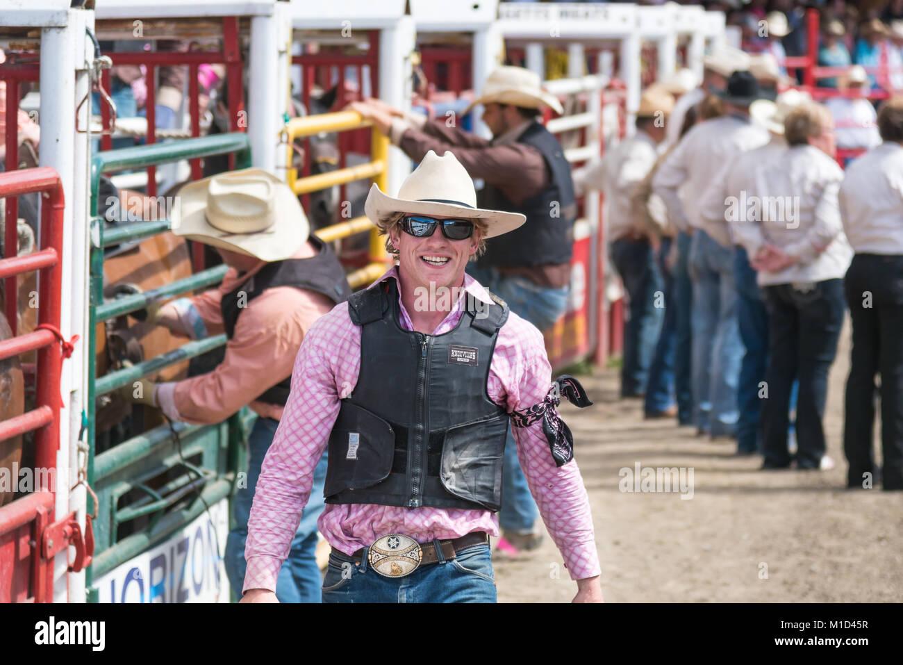 L'un des membres de l'équipe de course de cheval sauvage sourit aux photographes lors de la 90e Williams Lake Stampede, l'un des plus grands mouvements de panique en Amérique du Nord. Banque D'Images