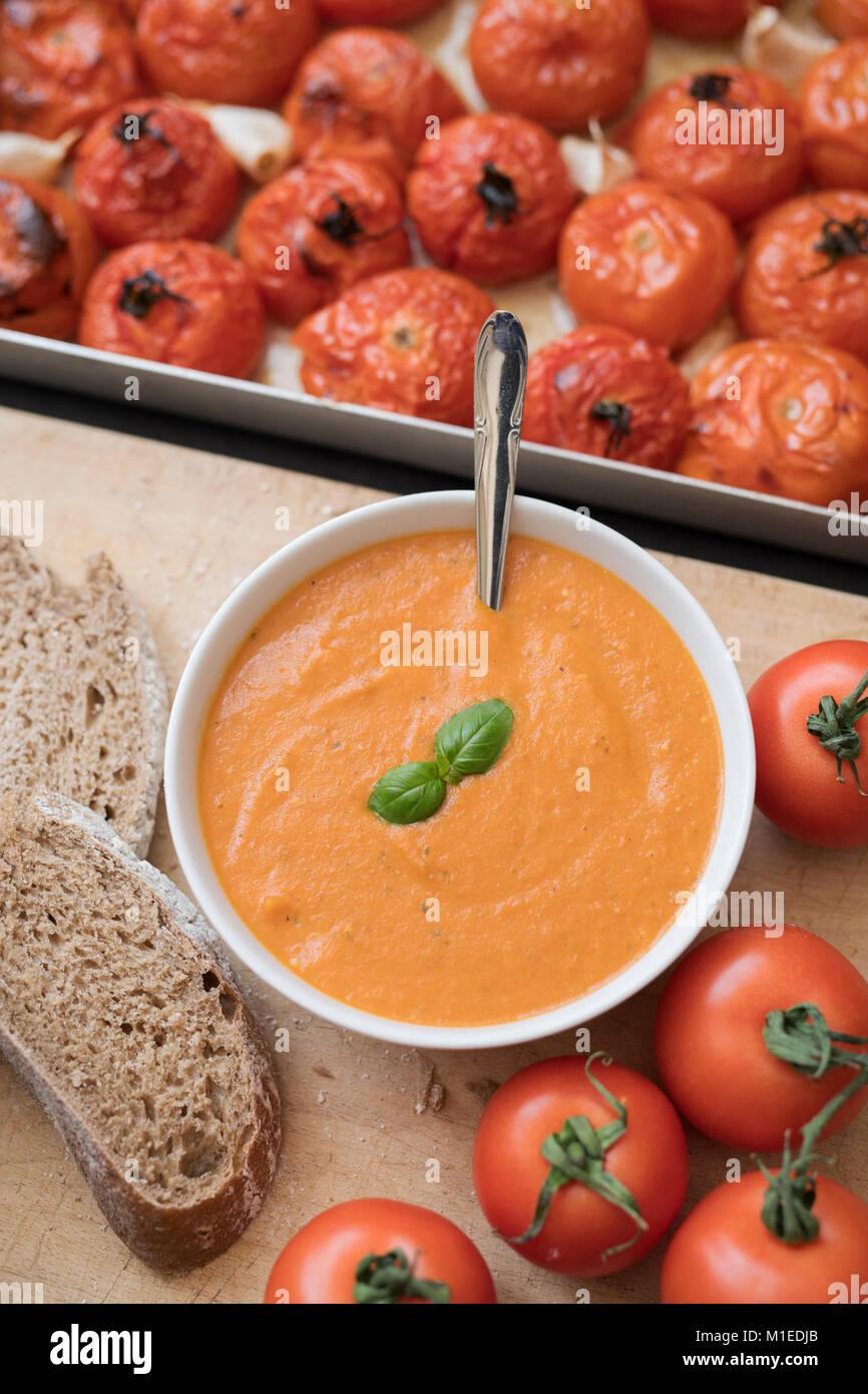 Soupe tomate et basilic fait maison avec du pain de seigle à côté de tomates grillées et l'ail Photo Stock