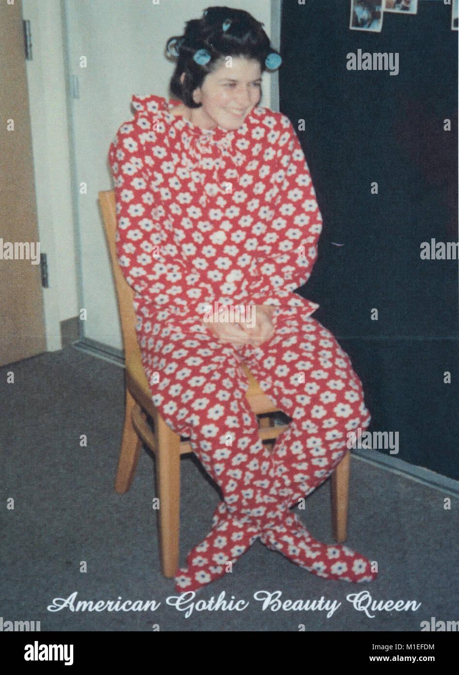 Adolescent avec des rouleaux dans les cheveux en une pièce portant des pyjamas à pieds, USA Photo Stock