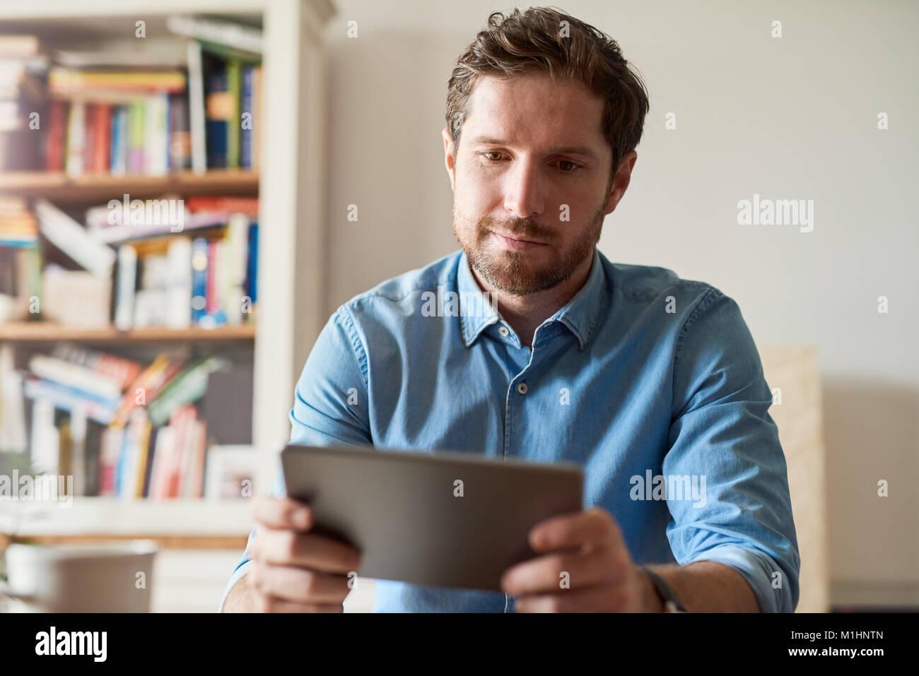 Jeune homme travailler à domicile à l'aide d'une tablette numérique Photo Stock