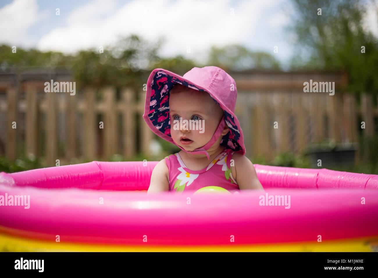 En rose bébé Hat assis dans piscine pour enfants Photo Stock