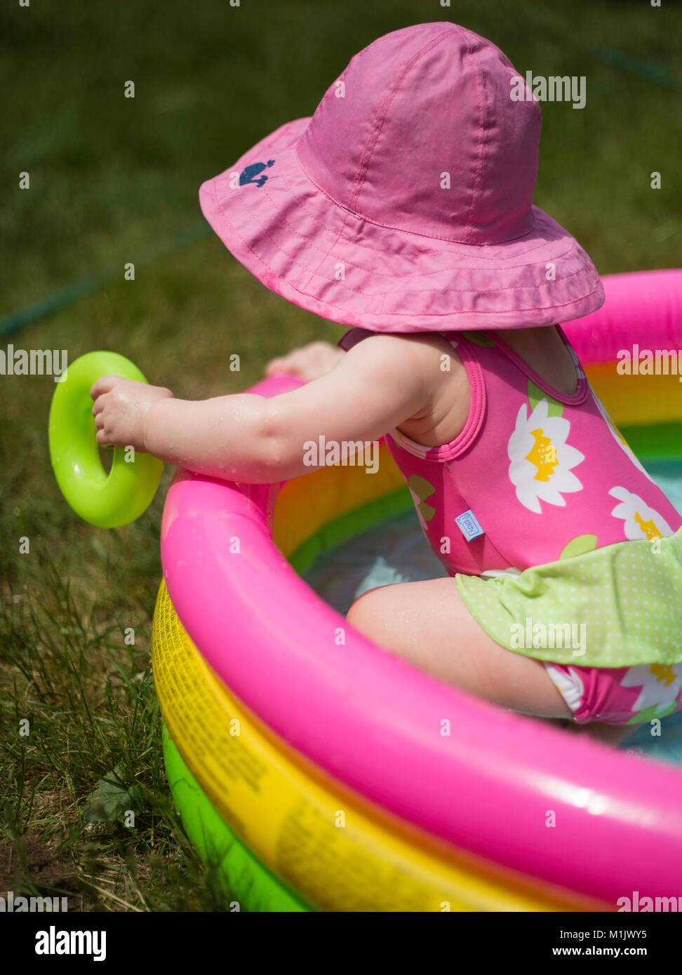 En rose bébé Hat jouant dans piscine pour enfants Photo Stock