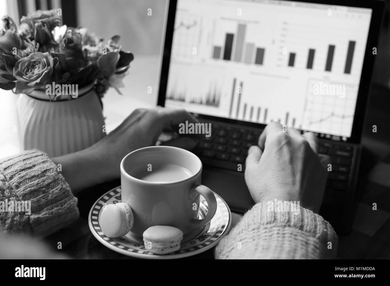 Vue de l'espace de travail avec une tasse de café avec du lait et deux délicieux macarons entre femme mains, travaillant sur l'ordinateur portable et d'un vase avec beautifu Banque D'Images