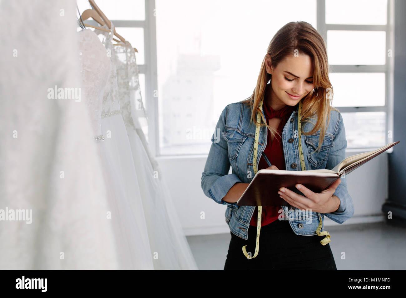 Designer de mode féminine travaillant dans robes de stocker et d'écrire dans un journal intime. Femme Photo Stock