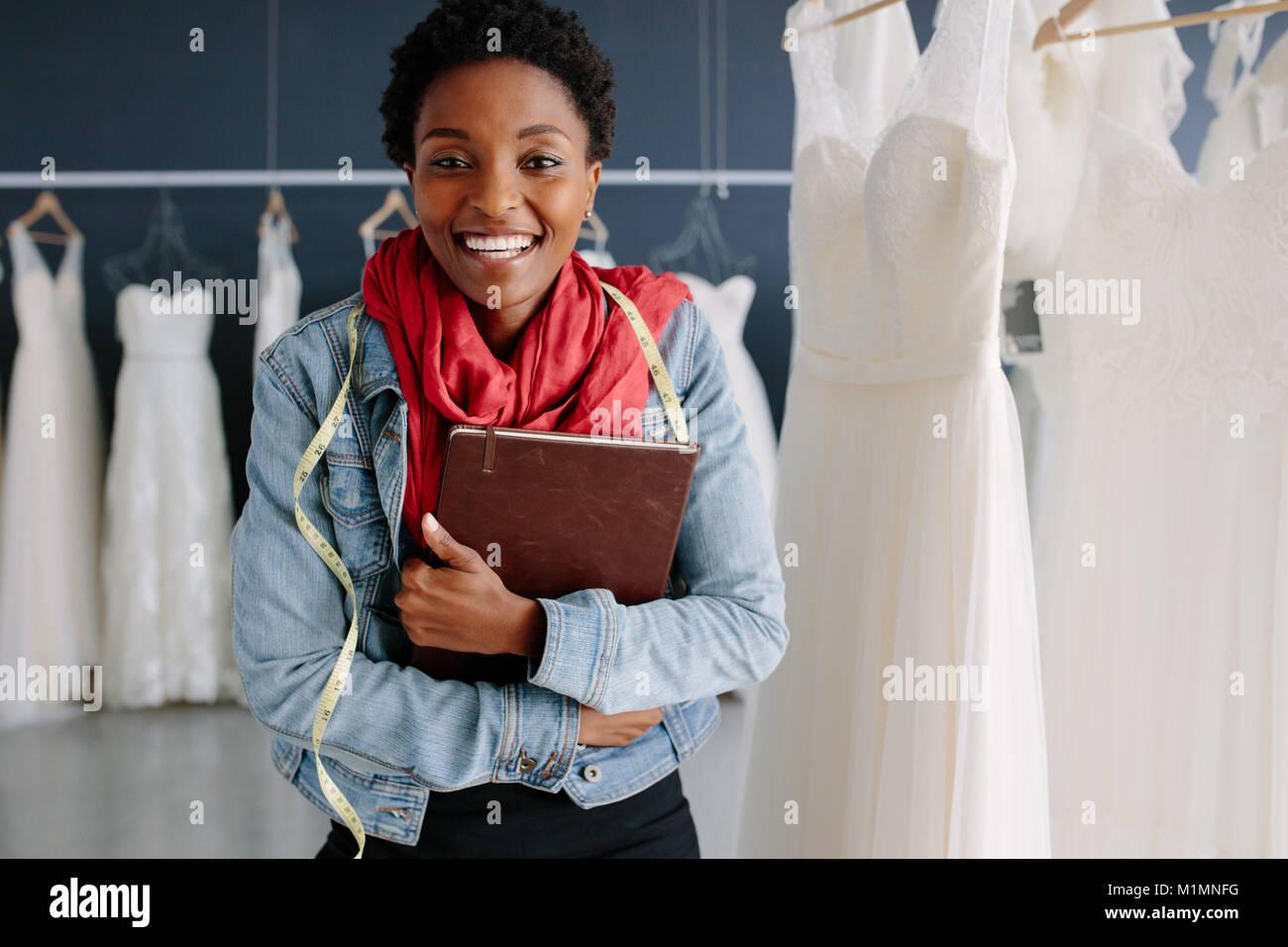 Cheerful bridal store owner standing dans sa boutique avec un journal intime. Mariage femme Fashion designer dans Photo Stock